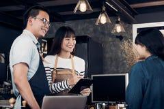 亚洲barista侍者和女服务员在咖啡馆,写饮料顺序的两个咖啡馆所有者接受从顾客的命令在逆酒吧,食物 免版税库存照片