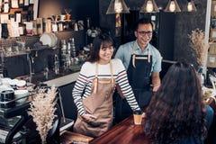 亚洲barista侍者和女服务员接受从顾客的命令cof的 库存图片