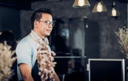 亚洲Barista侍者微笑和谈话与顾客在咖啡馆,在逆酒吧的咖啡馆所有者,食物和饮料企业概念,服务 图库摄影