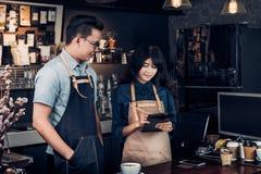 亚洲Barista侍者接受从顾客的命令咖啡店的,咖啡馆 免版税库存照片