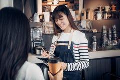 亚洲Barista侍者接受从顾客的命令咖啡店的,咖啡馆 库存照片