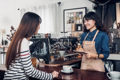 亚洲Barista侍者接受从顾客的命令咖啡店的,咖啡馆 库存图片