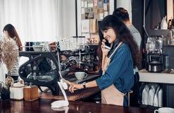 亚洲Barista用途片剂在咖啡馆接受从顾客,咖啡馆所有者写饮料顺序的在逆酒吧,食物和饮料的命令 库存照片