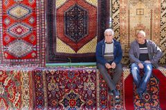 亚美尼亚人并且放松坐地毯在Vernissage市场上在耶烈万,亚美尼亚 免版税图库摄影