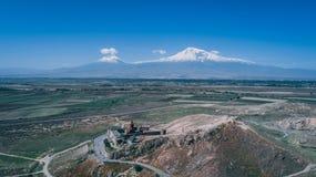 亚美尼亚教会的空中射击小山的与山阿勒山和清楚的天空蔚蓝 免版税库存照片