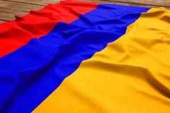 亚美尼亚的旗子木书桌背景的 丝绸亚美尼亚旗子顶视图 图库摄影