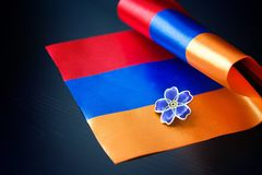 亚美尼亚种族灭绝一百周年纪念的勿忘草标志在亚美尼亚的奥斯曼帝国和旗子的 纪念日受害者  免版税库存照片
