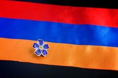 亚美尼亚种族灭绝一百周年纪念的勿忘草标志在亚美尼亚的奥斯曼帝国和旗子的 纪念日受害者  免版税库存图片