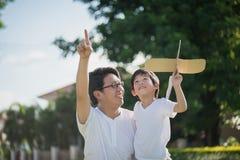 亚裔一起演奏纸板飞机的父亲和儿子 免版税库存图片