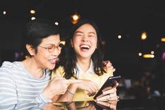 亚裔一起笑和微笑在selfie或象册的母亲和女儿,使用智能手机对餐馆或咖啡馆 图库摄影