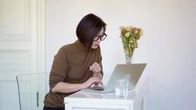 亚裔与膝上型计算机的妇女短的理发工作有在花瓶的花的