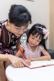 亚裔中国做家庭作业的母亲教的女儿 库存照片