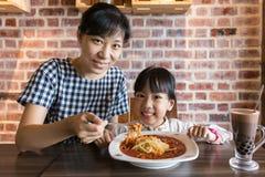 亚裔中国吃意粉博洛涅塞的母亲和女儿 免版税库存照片