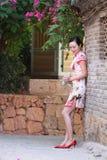 亚裔中国女孩在古镇佩带cheongsam享受业余时间 库存图片