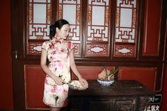 亚裔中国女孩在古镇佩带cheongsam享受业余时间 免版税库存图片
