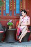 亚裔中国女孩在古镇佩带cheongsam享受假日 库存照片
