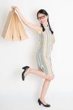 亚裔中国女孩递拿着纸购物袋 库存照片
