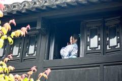亚裔中国女孩画象传统礼服的,佩带蓝色和白色瓷样式Hanfu,在楼上赢取前面的立场 库存图片
