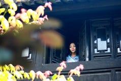 亚裔中国女孩画象传统礼服的,佩带蓝色和白色瓷样式Hanfu,在楼上赢取前面的立场 免版税库存图片