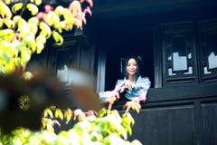 亚裔中国女孩画象传统礼服的,佩带蓝色和白色瓷样式Hanfu,在楼上赢取前面的立场 免版税图库摄影