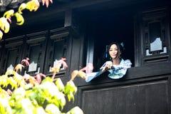 亚裔中国女孩画象传统礼服的,佩带蓝色和白色瓷样式Hanfu,在楼上赢取前面的立场 图库摄影