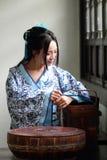 亚裔中国女孩画象传统礼服的,佩带蓝色,并且白色瓷样式Hanfu,在一个老厨房里运载食物箱子 免版税库存图片