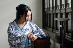 亚裔中国女孩画象传统礼服的,佩带蓝色,并且白色瓷样式Hanfu,运载一个传统食物箱子 库存图片