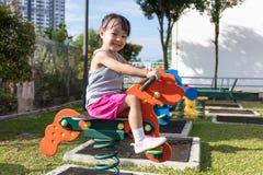 亚裔中国小女孩坐跷跷板 图库摄影