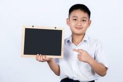 亚裔中国小男孩佩带的学生一致的指向的Chalkb 库存图片