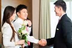 亚裔中国旅馆经理欢迎VIP客人 库存图片