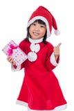 亚裔中国矮小的圣诞老人女孩对负当前与赞许 库存图片