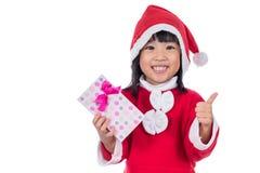 亚裔中国矮小的圣诞老人女孩对负当前与赞许 图库摄影