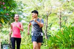 亚裔中国跑步在城市的男人和妇女停放 免版税库存图片