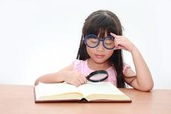 亚裔书女孩愉快的一点读取 免版税库存图片