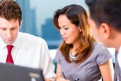 亚裔买卖人开会议在办公室 免版税库存照片
