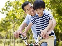 亚裔享受骑自行车的父亲和儿子户外 库存图片