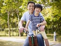 亚裔享受骑自行车的父亲和儿子户外 免版税库存图片