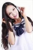 亚裔享用的音乐女小学生 免版税库存图片