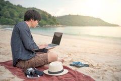 年轻亚裔人与在海滩的膝上型计算机一起使用 库存图片