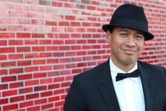 年轻亚裔人佩带的无尾礼服和一个花梢帽子画象  免版税库存图片
