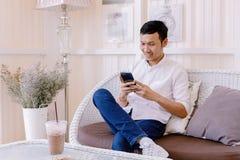亚裔人使用一个手机的和饮料咖啡在面包店购物 库存图片