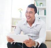 亚裔人听与耳机的音乐 库存照片