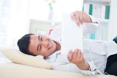 亚裔人听在沙发的歌曲 库存照片