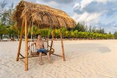 亚裔人在摇摆放松在海滩 免版税图库摄影