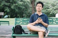 亚裔人坐与耳机的长凳在庭院里 库存图片
