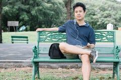 亚裔人坐与耳机的长凳在庭院里 免版税图库摄影