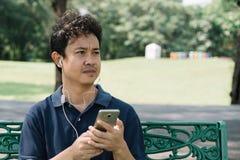 亚裔人坐与耳机的长凳在庭院里 免版税库存照片