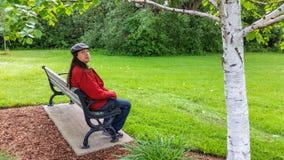 亚裔人坐回顾的长凳 图库摄影
