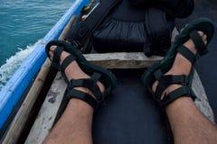 亚裔人坐的坐运河船在看和享受河生活方式视图的浮动市场上在她期间佩带的凉鞋wi 库存图片