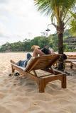 亚裔人垂直的照片在海滩放松 免版税图库摄影